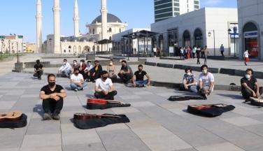 Müzisyenler sessiz oturma eylemi yaptı enstürmanlarını yere bıraktı